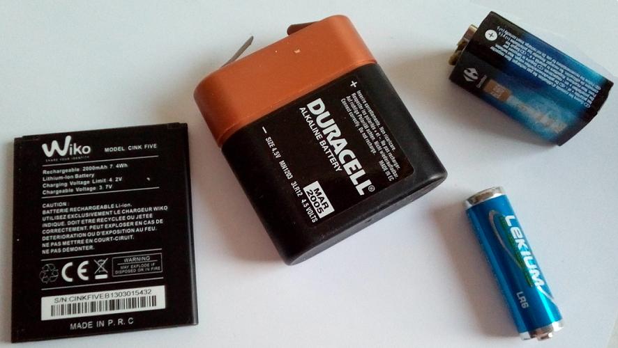 Fig. 1: Exemple de piles et batteries. De gauche à droite : Une batterie de Smartphone Li-ions, 4,2V, 2Ah, 7.4Wh. Puis trois types de piles alcalines, une pile de 4,5V. Une pile de 1,5V. Une pile de 9V, 0,55Ah