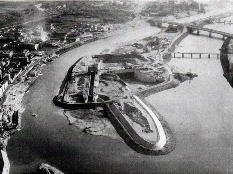 Fig. 6 : Vue du chantier écluse-déchargeur-usine depuis l'amont. En haut à droite on aperçoit le barrage déjà en eau. Source: Cazenave P. (1967). L'usine hydroélectrique de Pierre-Bénite, in revue Travaux, octobre 1967.